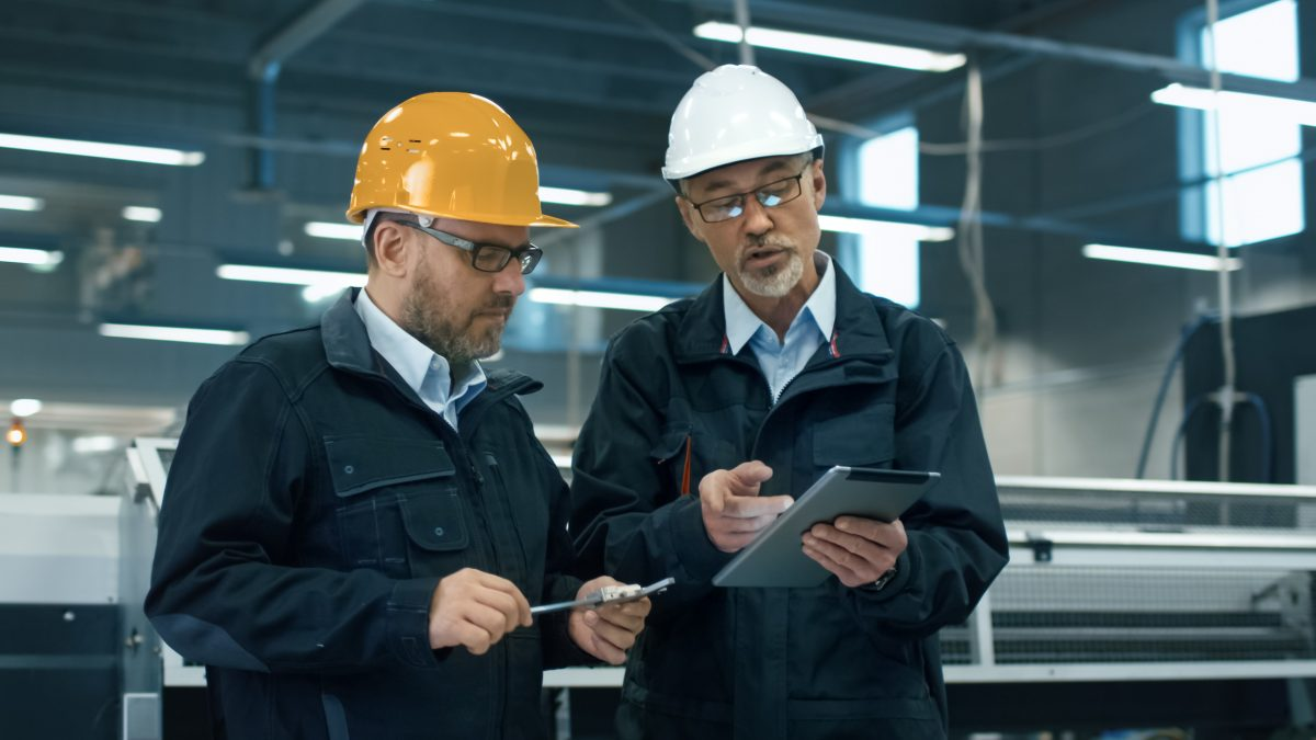 Two engineers in hardhats discuss an osha compliance checklist