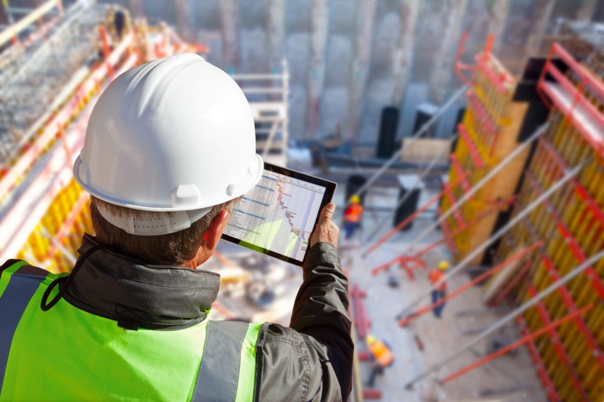 Quality manager adding data to a tablet on a construction work site