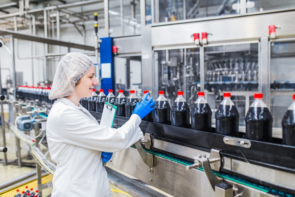 Quality manager inspects bottle seals during an ISO 9001 quality management process
