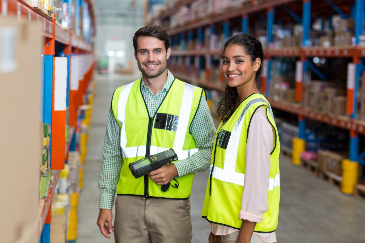 Two smiling warehouse employees at work in an organized and clean space