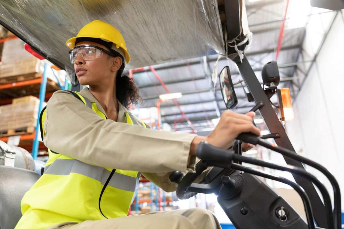 female warehouse worker learning to drive a forklift