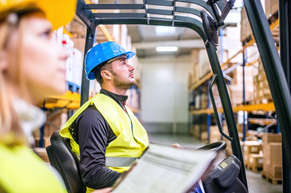 Young workers working together. Man forklift driver and a woman in a warehouse.