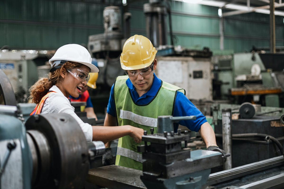 man and woman working in factory with ppe