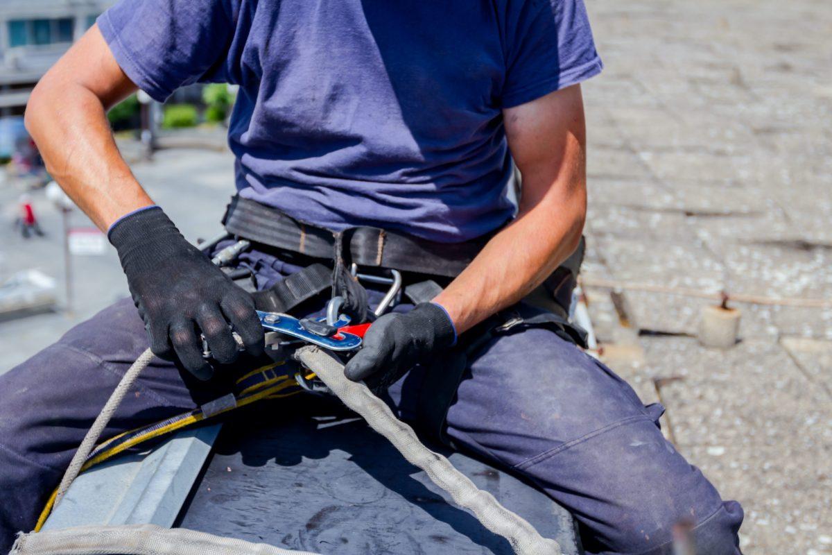 worker adjusting his fall arrest system during hazardous rooftop installation