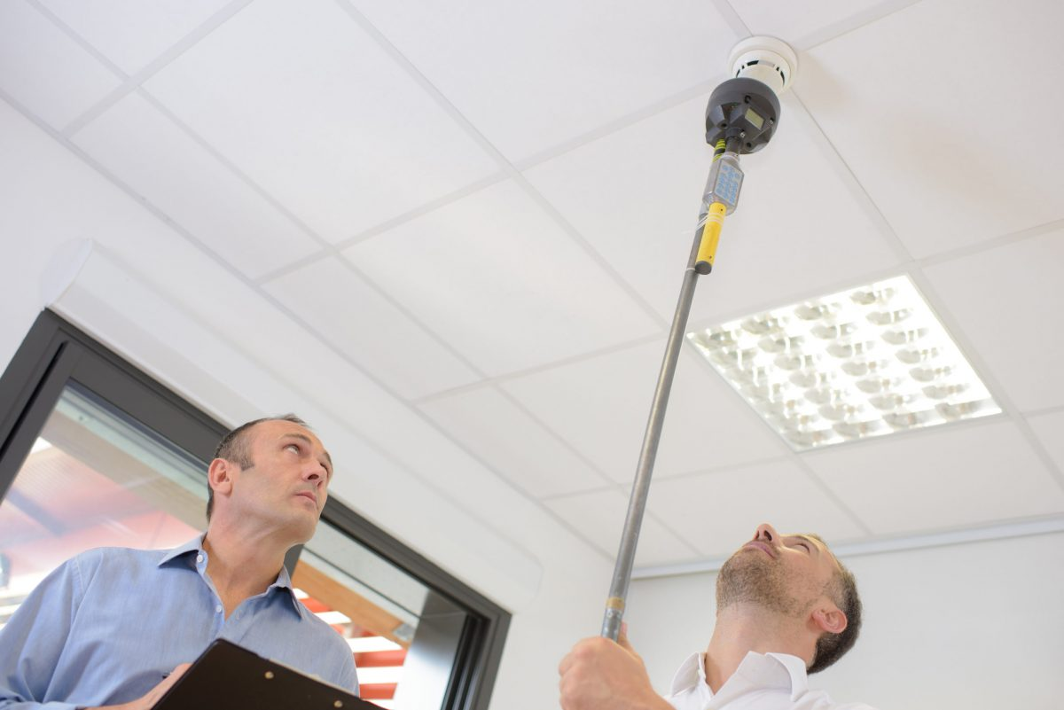 two men inspect a smoke alarm from the ground due to hierarchy of controls
