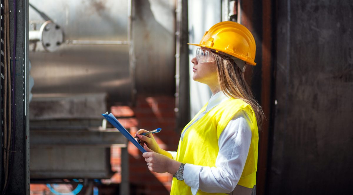 female safety coordinator in hardhat with a clipboard