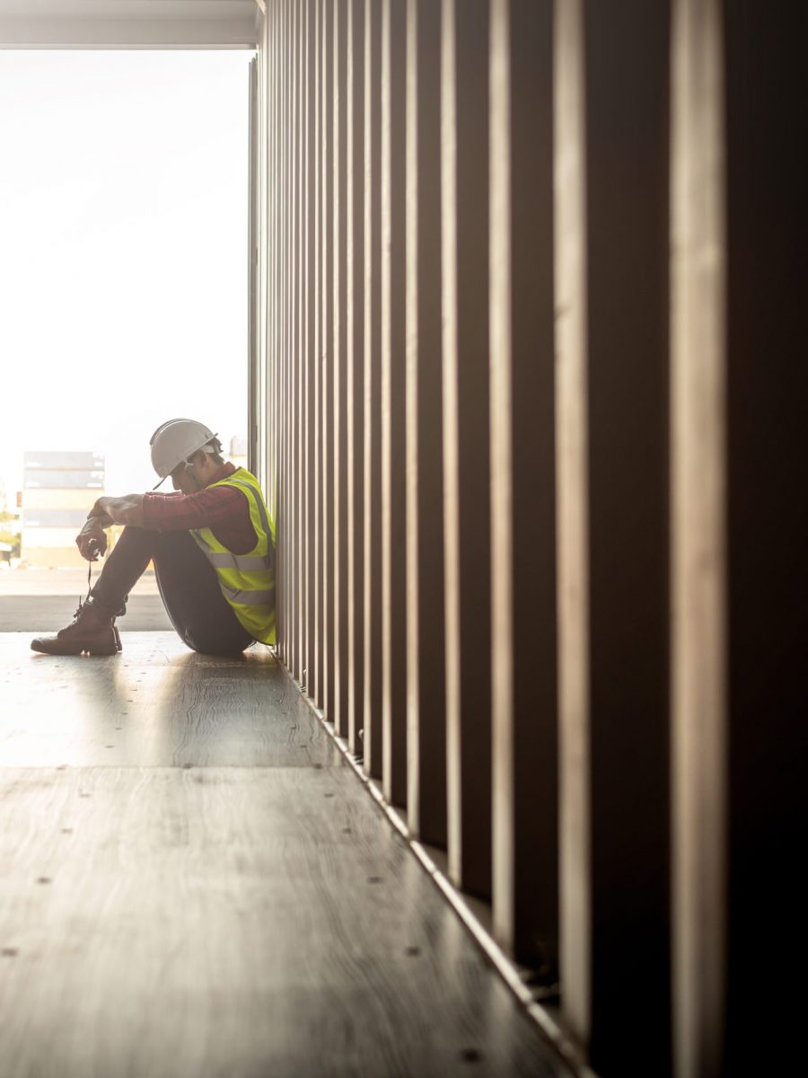 stressed worker sitting in a shipping container