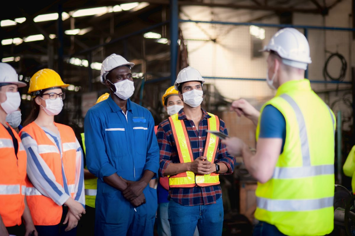 A Team Of Technicians, Foreman And Engineers Accepting Assignments From A Manager Or Supervisor In The Morning Meeting Before Work In Which Everyone Wear Surgical Masks To Prevent The Coronavirus