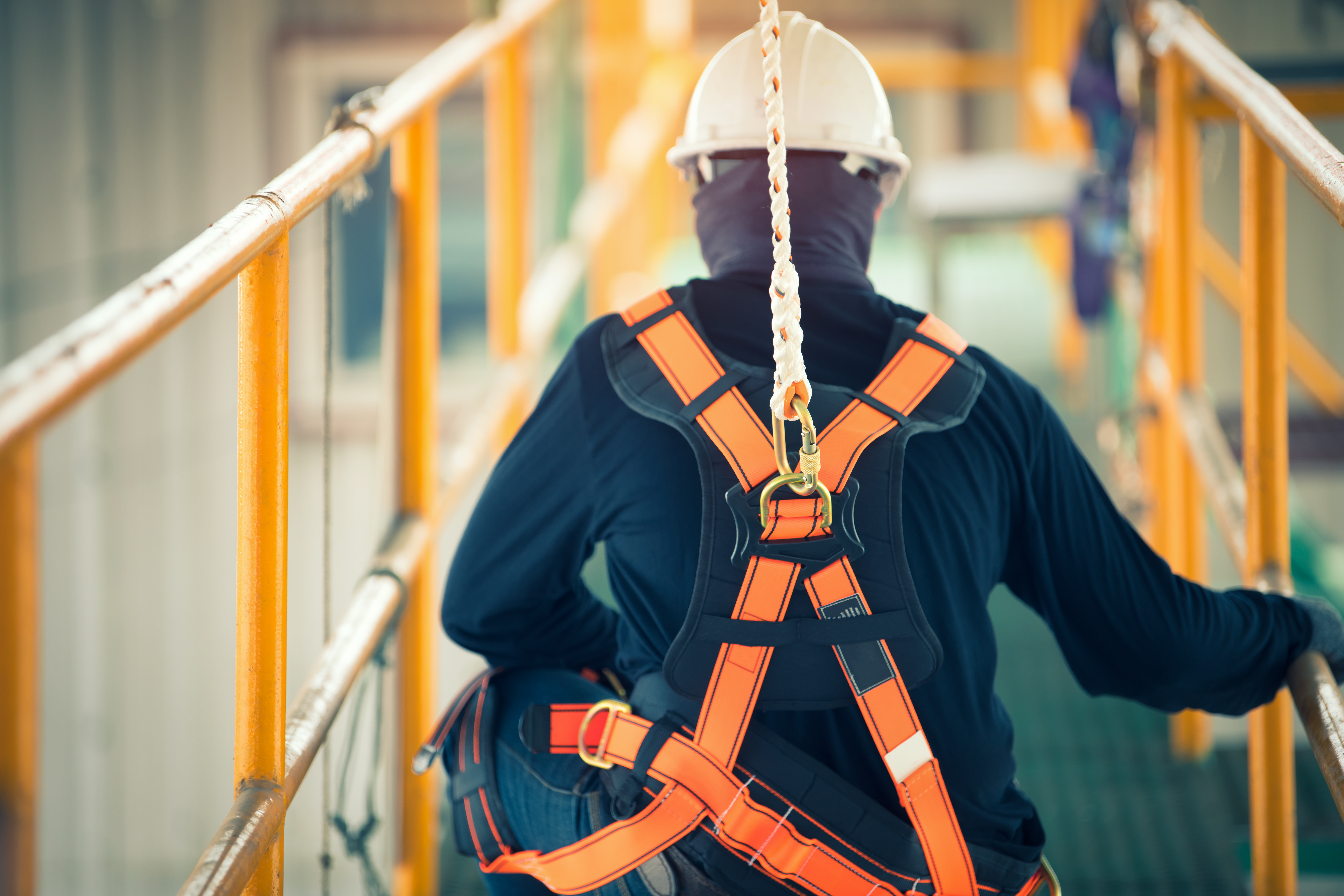Construction worker following safety management plan wearing harness at heights