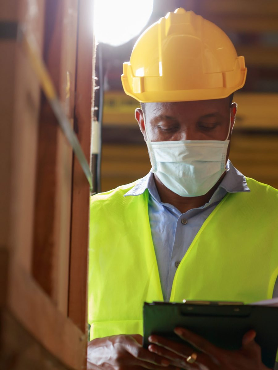 Young Black African Male Worker Wearing Protective Face Mask Working In Factory Warehouse. Black Man Checking Stock During Covid 19 Pandemic Crisis. Logistic Industry Concept.
