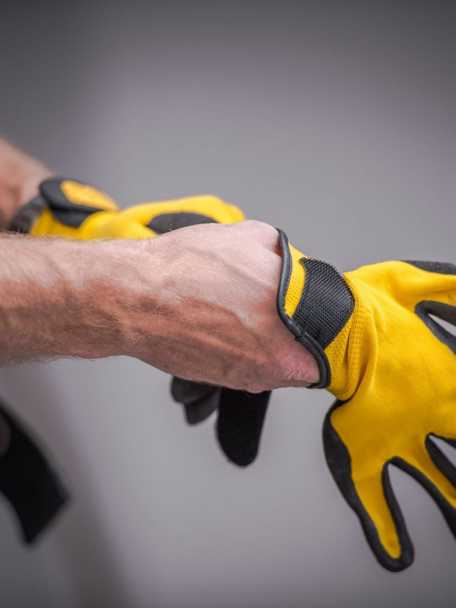 Worker putting on yellow safety gloves