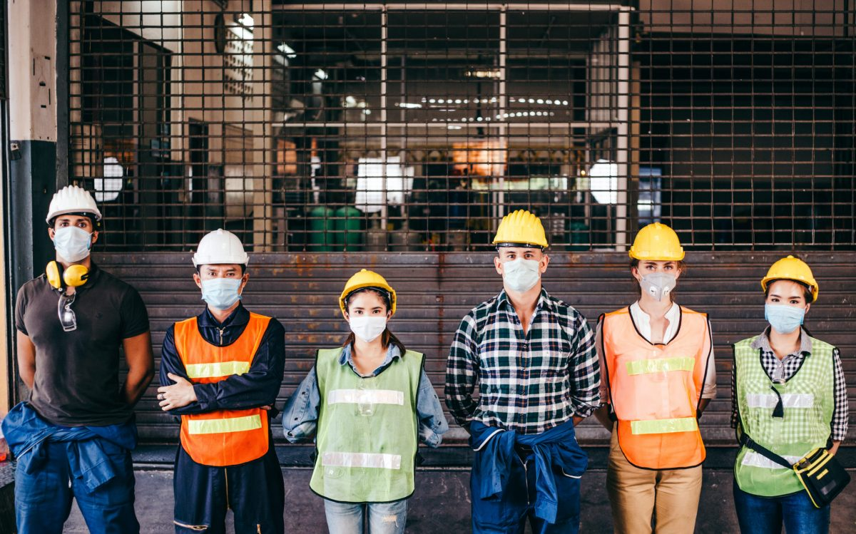 Group Of Industrial Or Engineer Corporate Workers Wear Protective Mask And Hard Hat Helmet Standing Line Up In Front Of Factory Lock Down Prevention For Coronavirus Or Covid 19 Epidemic Outbreak