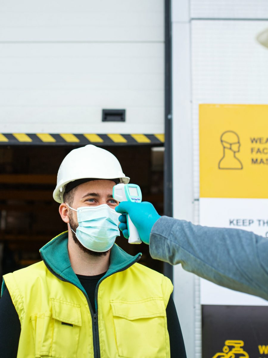 Workers With Face Mask In Front Of Warehouse, Coronavirus And Temperature Measuring Concept.