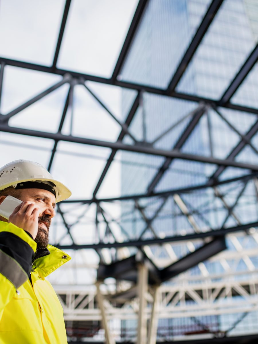 Safety professional communicating with subcontractors on the pone