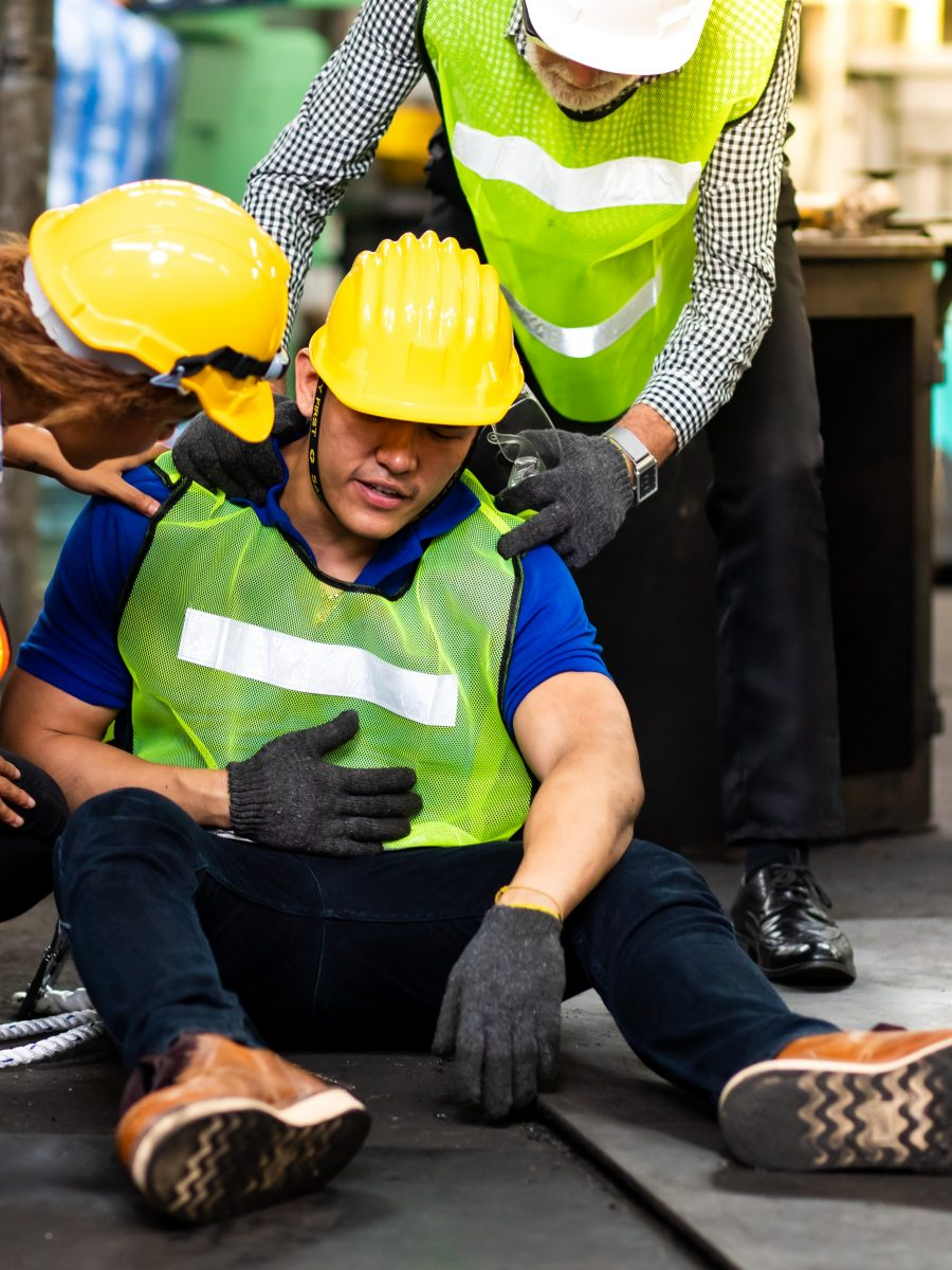 First Aid. Engineering Supervisor Talking On Walkie Talkie Communication While His Coworker Lying Unconscious At Industrial Factory. Professional Engineering Teamwork Concept.