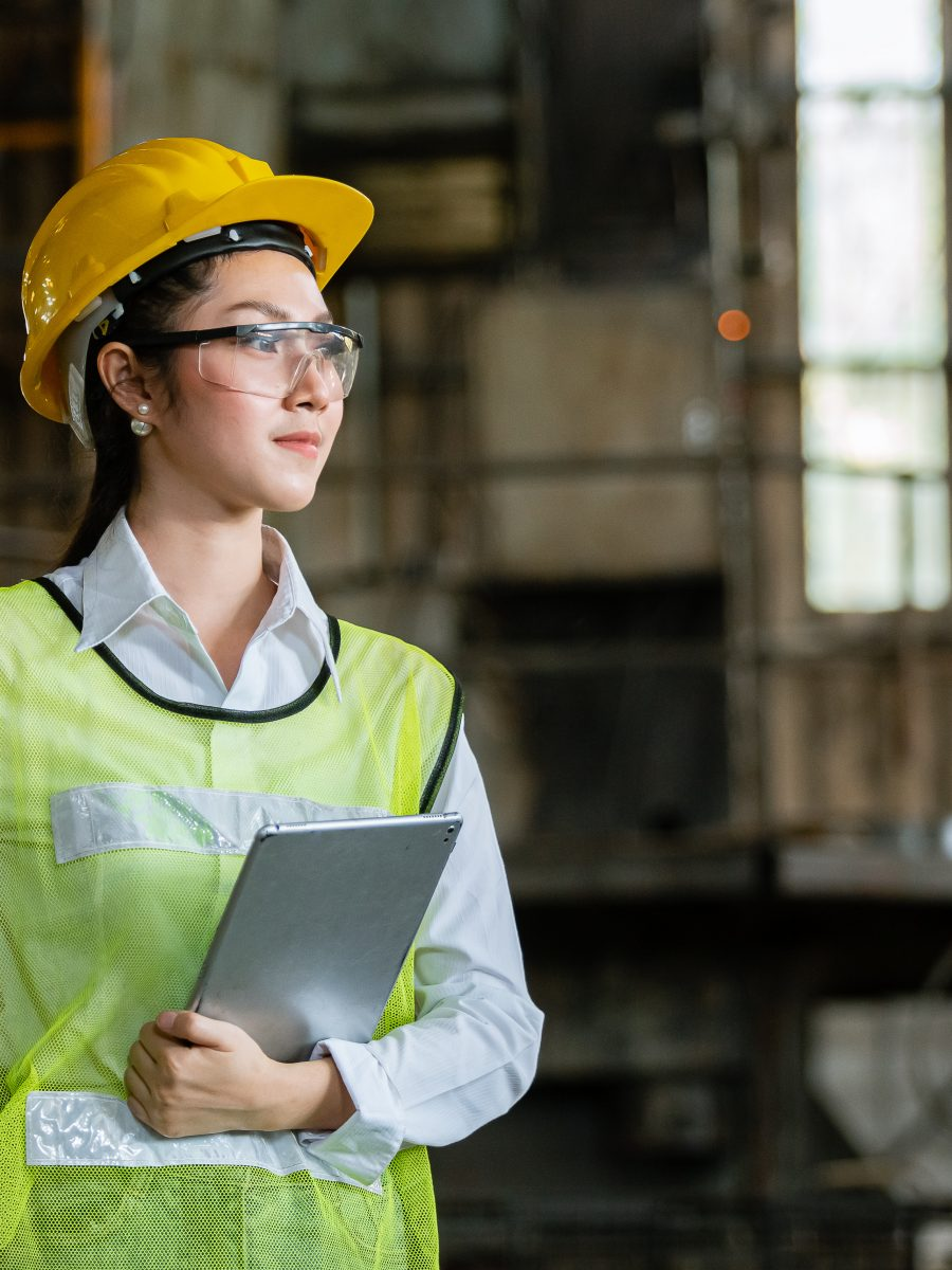 Asian Woman Engineer Industry Heavy Worker Wearing Hardhat And Holding Tablet Standing At Machine Area In Factory, Engineering Industrial Concept.